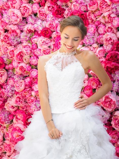 Schöne braut in einem hochzeitskleid, das auf dekorative rosa blumen aufwirft. Premium Fotos