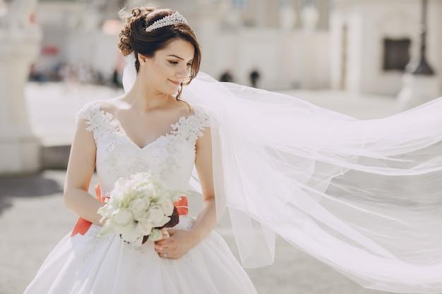Schöne braut in einem weißen kleid und eine krone auf seinem kopf in einem park und blumenstrauß halten Kostenlose Fotos