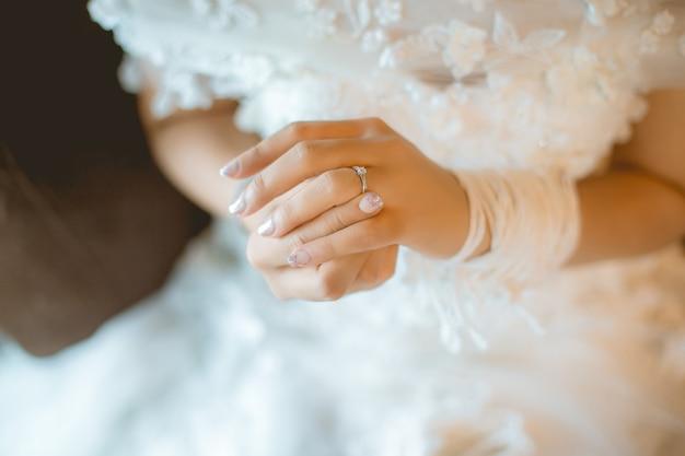 Schöne braut mit weißem hochzeitskleid halten ihren ehering im glatten gefühl. Premium Fotos