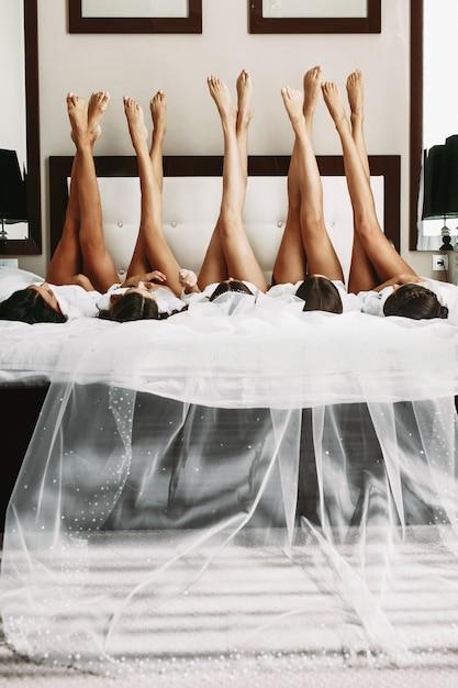 Schöne braut u. brautjungfern, die sexy beine auf bett vorführen Kostenlose Fotos