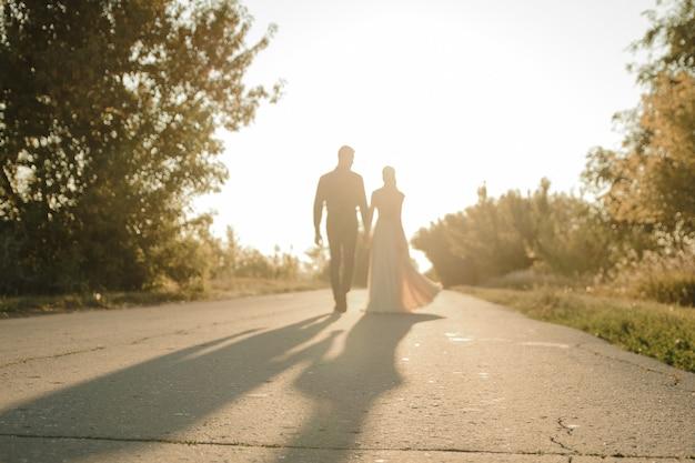 Schöne braut und bräutigam gehen gegen die sonne. zwei liebende umarmen und küssen sich Premium Fotos