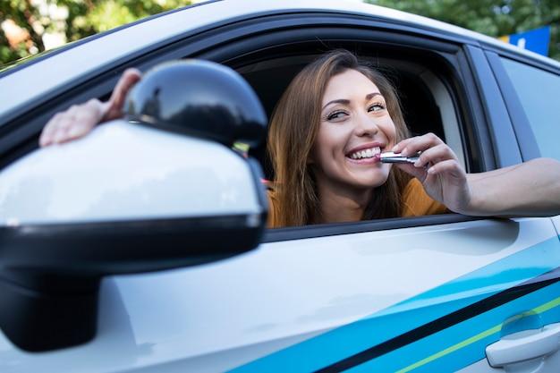 Schöne brünette frau, die im auto sitzt und sich hübsch macht, indem sie lippenstift verwendet, der make-up anwendet Kostenlose Fotos
