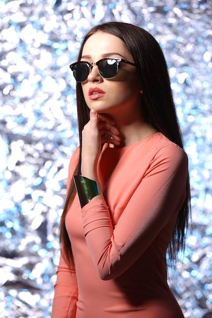 Schöne brünette frau mit sonnenbrille und langen haaren posiert Premium Fotos
