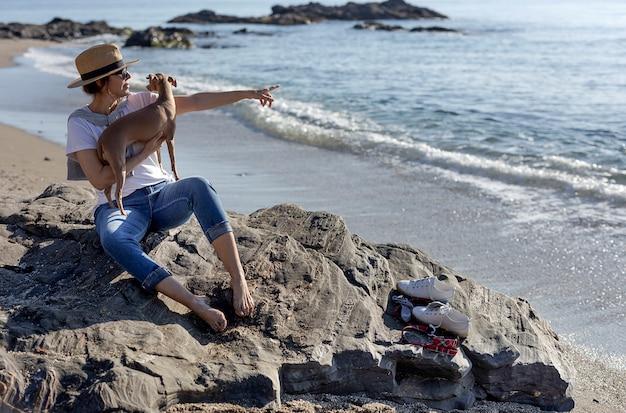 Schöne brünette frau spielt mit hund am strand Premium Fotos