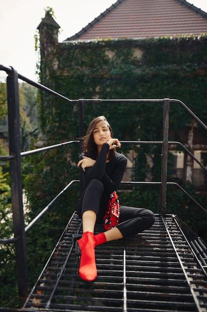 Schöne brünette posiert auf einem schwarzen treppenhaus Kostenlose Fotos