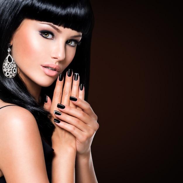 Schöne brunetfrau mit schwarzen nägeln und mode-make-up der augen. mädchen mit gerader frisur im studio Kostenlose Fotos