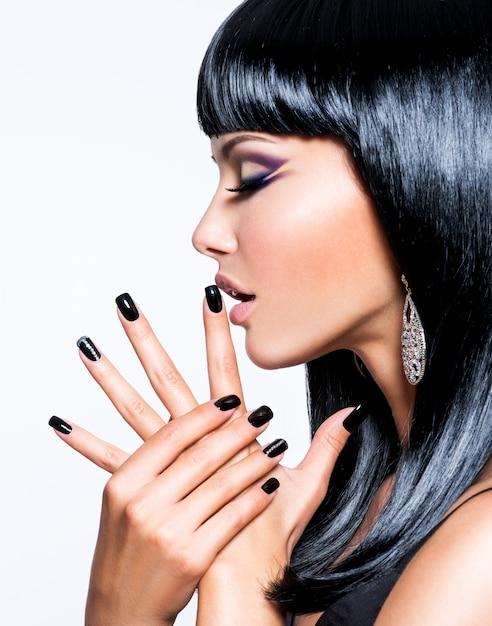 Schöne brunetfrau mit schwarzen nägeln und mode-make-up der augen Kostenlose Fotos