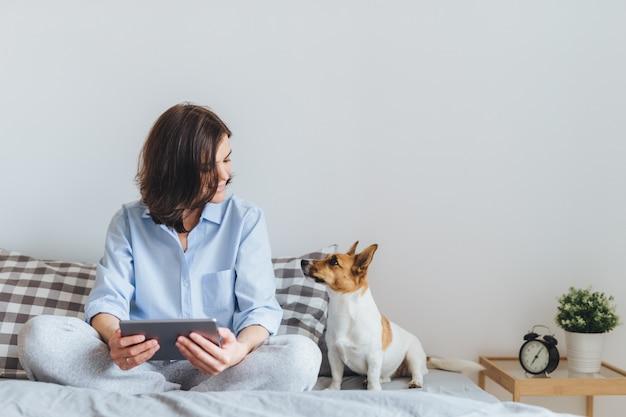 Schöne brunettefrau in den pyjamas sitzt auf bett im schlafzimmer mit ihrem jack- russellterrierhund. Premium Fotos