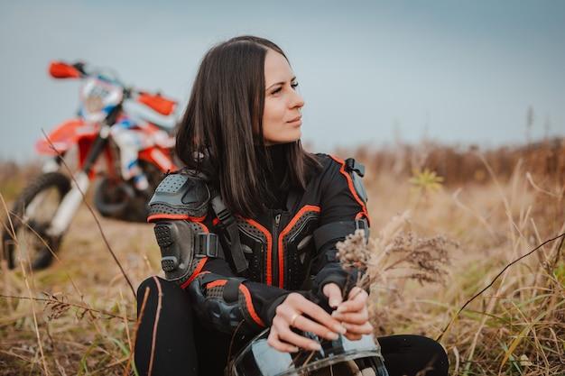 Schöne brunettefrau in der motorradausstattung. motocross-rennfahrerin neben ihrem motorrad Premium Fotos