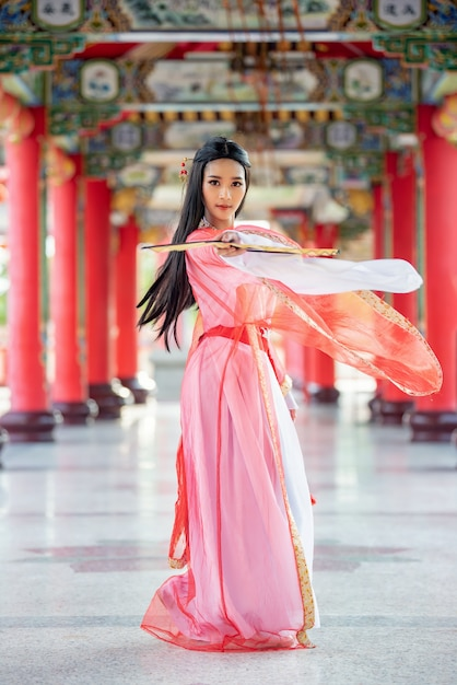 Schöne chinesische frau mit einer traditionellen klage mit schlag in ihren händen. Premium Fotos