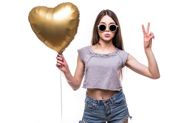 Schöne dame der fröhlichen brünetten im kleid, die luftballon wie herz hält und friedensgeste lokalisiert zeigt Kostenlose Fotos
