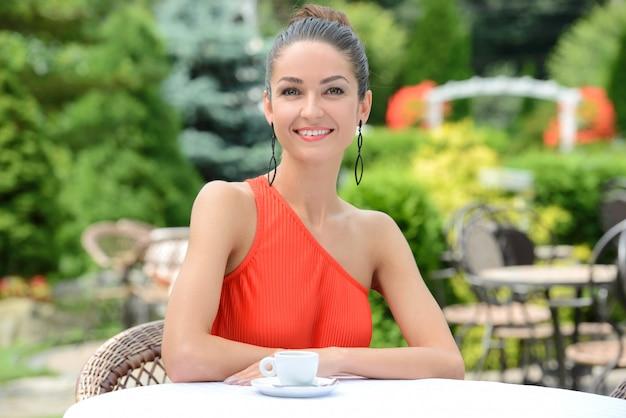 Schöne dame im bunten kleid, trinkender kaffee. Premium Fotos