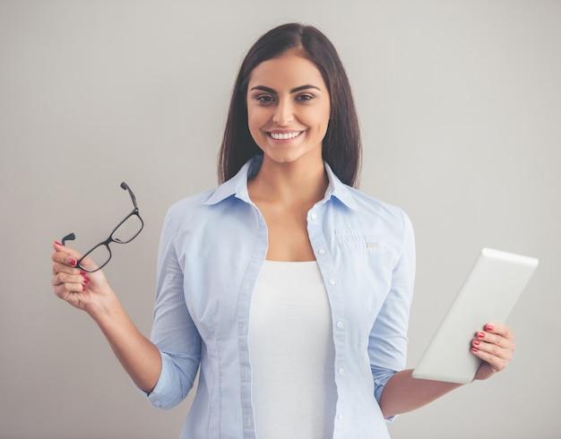 Schöne dame in der intelligenten freizeitkleidung benutzt digitale tablette. Premium Fotos