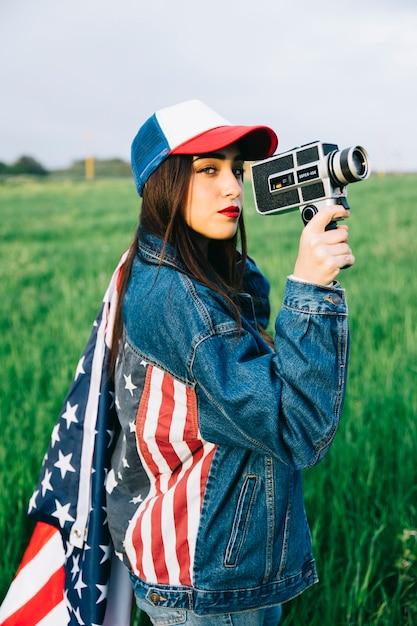 Schöne dame mit der retro- kamera, die auf dem gebiet bleibt Kostenlose Fotos