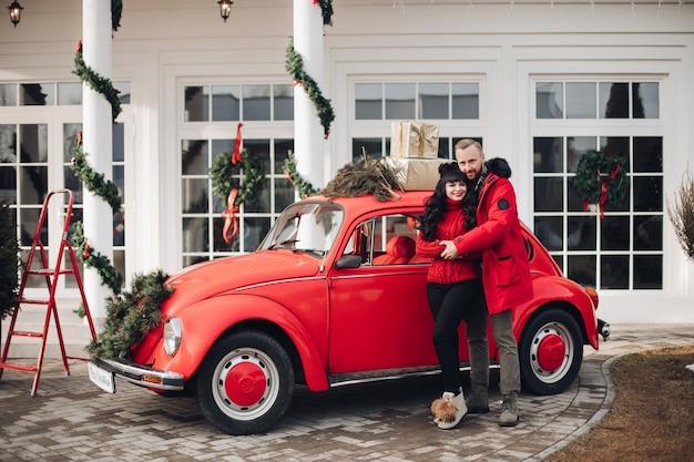Schöne dame und ihr freund umarmen sich durch ein rotes auto, das in der nähe eines hauses mit weihnachtsschmuck geparkt wird Kostenlose Fotos