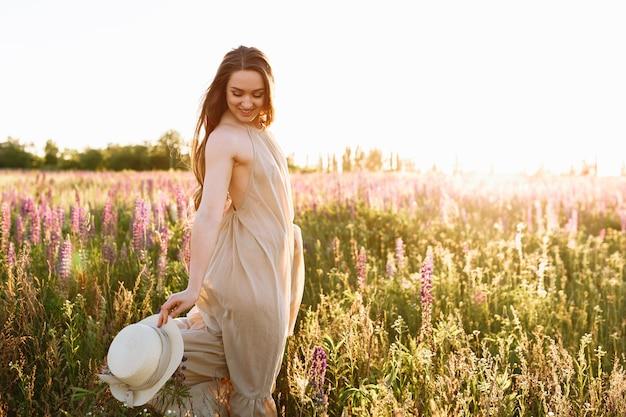 Schöne dunkelhaarige frau in einem sommerkleid auf einem gebiet von blühenden lupineblumen Kostenlose Fotos