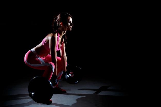 Schöne eignungsfrau, die hocken mit einem barbell tut Premium Fotos