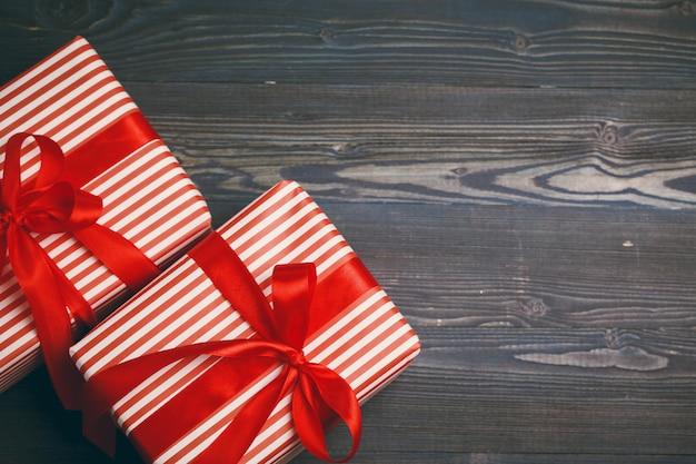 Schöne eingewickelte geschenke auf dunklem hölzernem hintergrund Premium Fotos