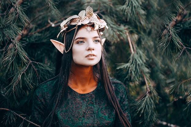 Schöne elfenfrau, feenwald mit den langen ohren, goldene kranzkrone des langen dunklen haares auf kopf Premium Fotos