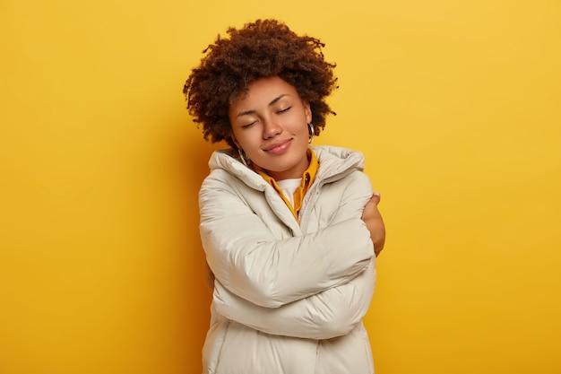 Schöne erfreute frau genießt komfort in neuer winterjacke, umarmt sich, hält die augen geschlossen, fühlt sich warm und zufrieden, har lockige frisur, isoliert über gelbem hintergrund. menschen, kleidungskonzept Kostenlose Fotos