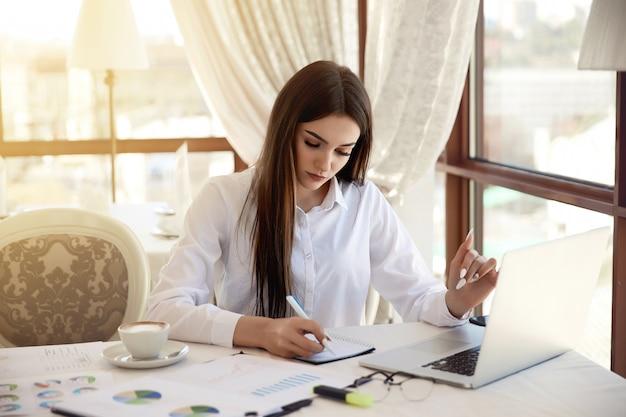 Schöne ernste frau schreibt etwas zum notizbuch an ihrem arbeitsplatz Kostenlose Fotos