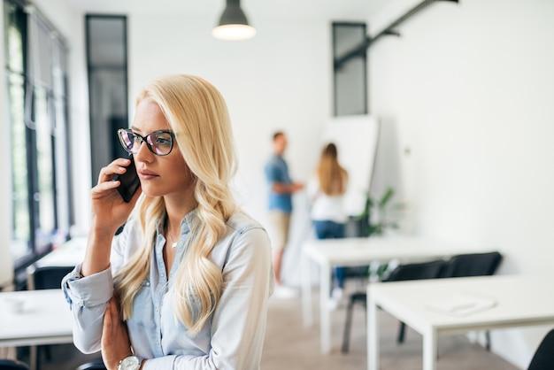 Schöne ernste geschäftsfrau, die einen telefonanruf bei der arbeit hat. Premium Fotos