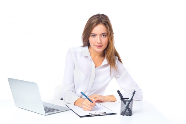 Schöne ernste junge geschäftsfrau, die am tisch lokalisiert über weißem hintergrund sitzt Premium Fotos