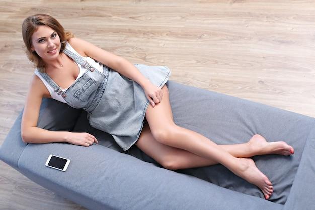 Schöne erwachsene frau, die in der couch liegt Kostenlose Fotos
