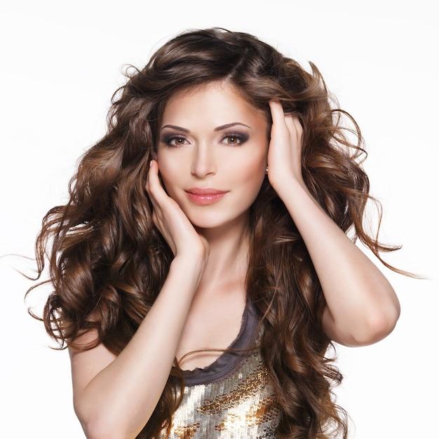 Schöne erwachsene frau mit langen braunen lockigen haaren. modemodell über weißem hintergrund Kostenlose Fotos