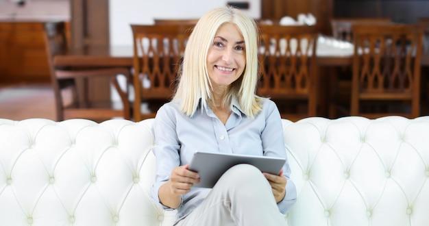 Schöne fällige frau, die zu hause elektronische tablette verwendet Premium Fotos
