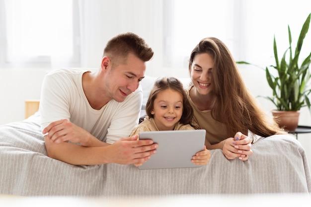 Schöne familie, die eine tablette betrachtet Kostenlose Fotos