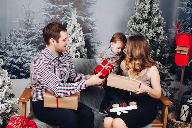 Schöne familie, die zusammen auf bank sitzt und weihnachtsgeschenke vor feiertagen genießt Premium Fotos