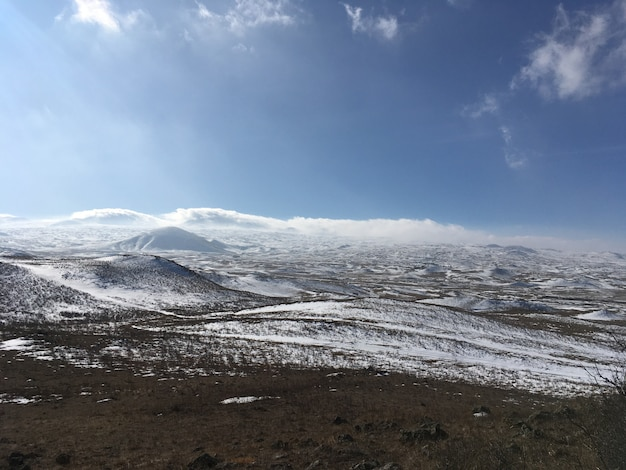 Schöne felder bedeckt mit schnee und erstaunlich bewölktem himmel Kostenlose Fotos