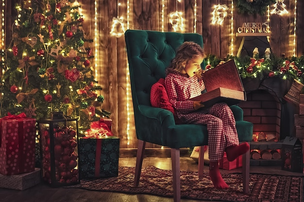 Schöne ferien. nettes kleines kinderöffnungsgeschenk nahe weihnachtsbaum. das mädchen lacht und genießt das geschenk. Premium Fotos