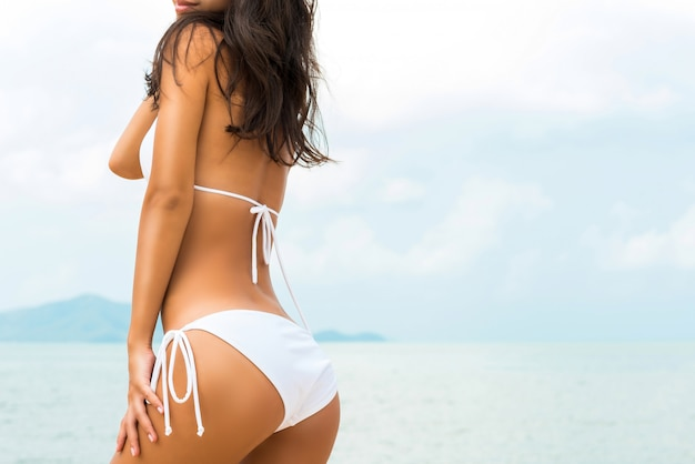 Schöne formfrau im weißen bikinibadeanzug, der am strand aufwirft Premium Fotos