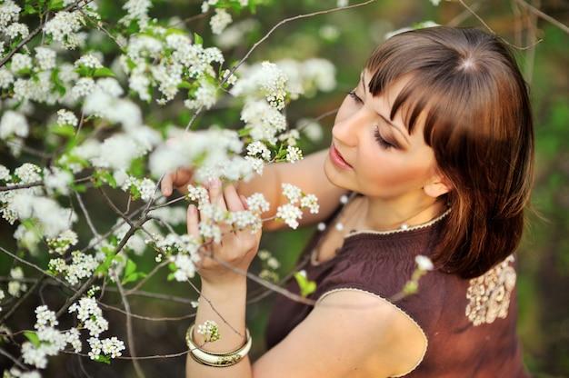 Schöne frau auf der natur nahe blühenden bäumen Premium Fotos