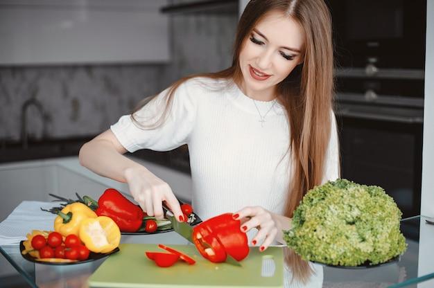 Schöne frau bereiten lebensmittel in einer küche zu Kostenlose Fotos