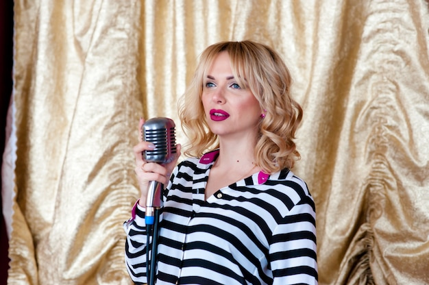 Schöne frau, blondine, mikrofon. gesang, schönes lächeln Premium Fotos