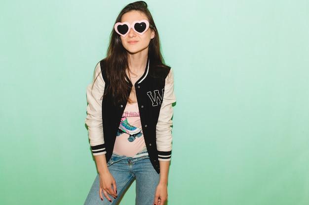 Schöne frau des jungen hipsters, lustige herzsonnenbrille, gegen blaue wand, kühler gesichtsausdruck Kostenlose Fotos