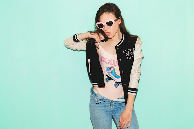Schöne frau des jungen hipsters, lustige herzsonnenbrille, gegen blaue wand, nicht isoliert, kühler gesichtsausdruck Kostenlose Fotos