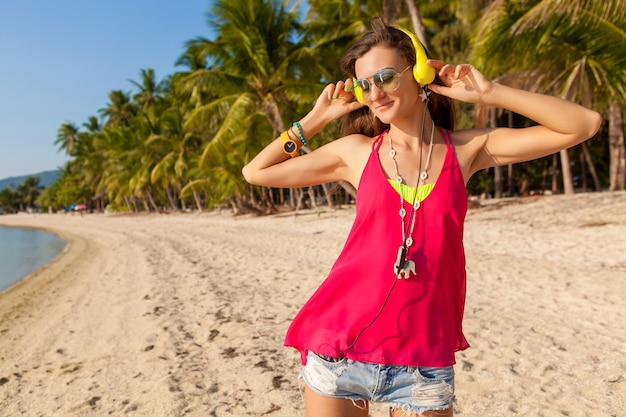 Schöne frau des jungen hipsters, tropischer strand, urlaub, bunt, sommertrendstil, sonnenbrille, kopfhörer, musik hören, palmenhintergrund, glücklich lächelnd, spaß, details, nahaufnahmeporträt Kostenlose Fotos