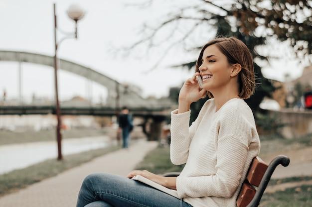 Schöne frau, die am telefon im stadtpark spricht. Premium Fotos