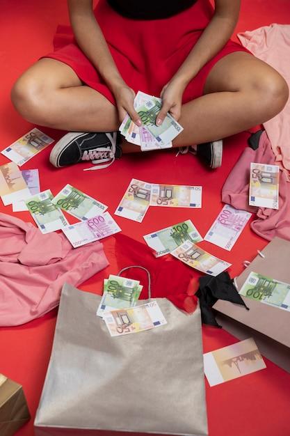 Schöne frau, die auf dem boden mit geld sitzt Kostenlose Fotos