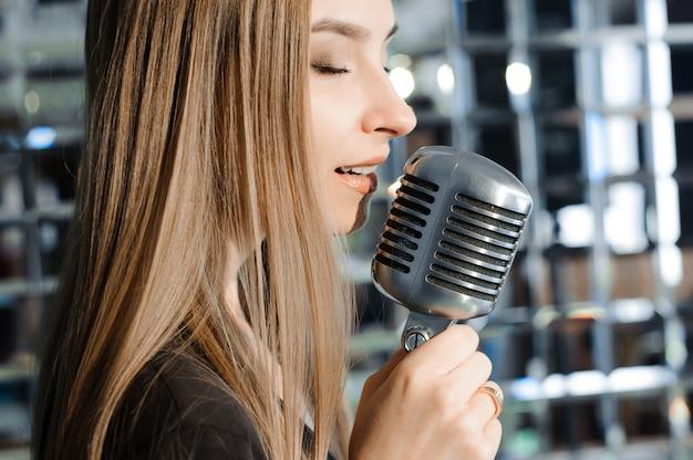 Schöne frau, die auf der bühne neben dem mikrofon singt. Premium Fotos