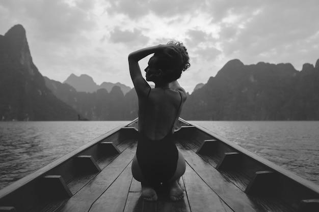 Schöne frau, die auf einem boot aufwirft Kostenlose Fotos