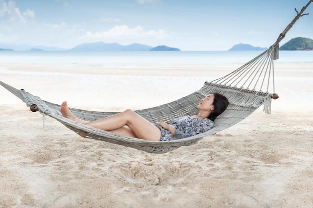 Schöne frau, die auf hängematte am strand schläft, moment von der berufung. Premium Fotos