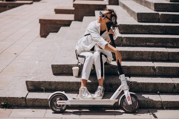Schöne frau, die auf treppen mit ihrem roller sitzt Kostenlose Fotos
