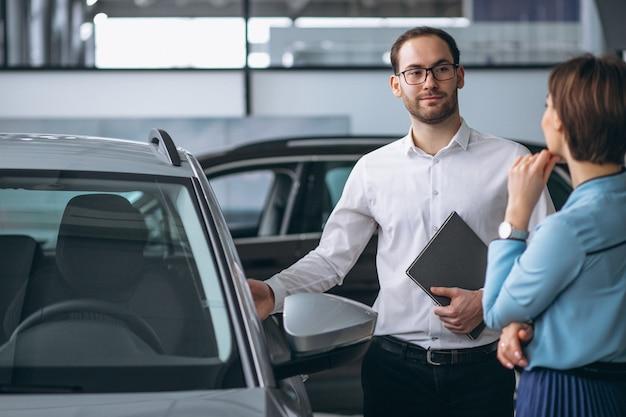Schöne frau, die ein auto kauft Kostenlose Fotos
