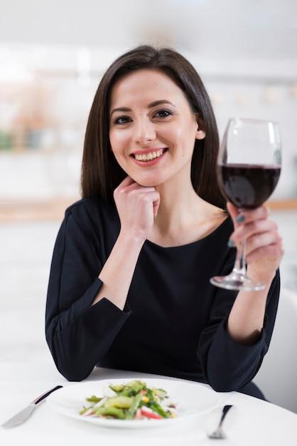 Schöne frau, die ein glas rotwein hält Kostenlose Fotos