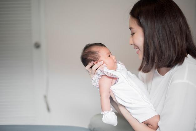 Schöne frau, die ein neugeborenes schätzchen in ihren armen anhält Premium Fotos